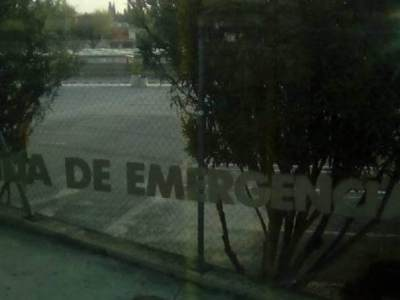 """Una ventana en donde se lee """"salida de emergencia"""" se ven árboles"""
