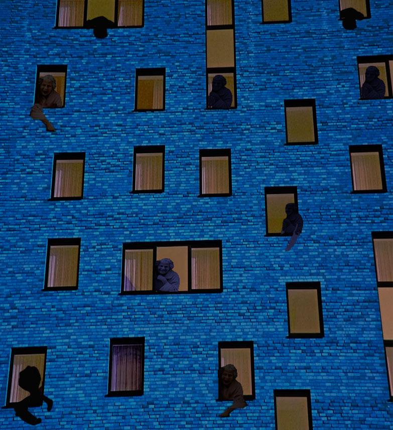 ventanas de un gran edificio azul enfrente del Piso de Daniel con gente asomada y gritando